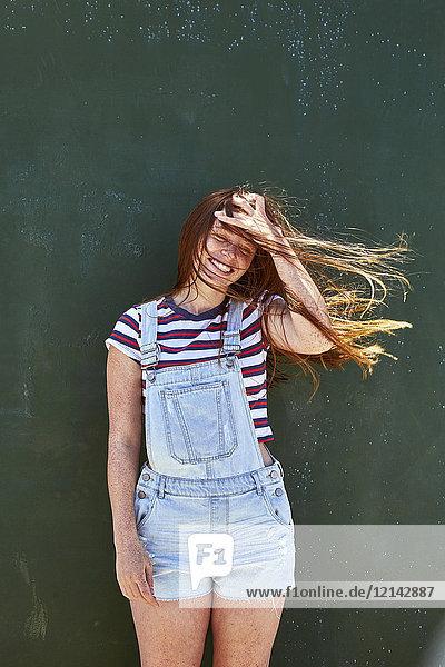 Fröhliche junge Frau mit windgepeitschten Haaren steht vor grüner Wand