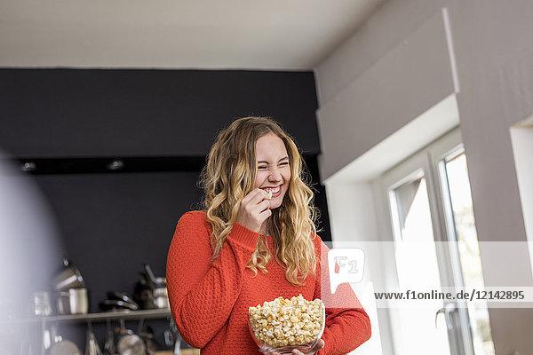 Porträt einer kichernden jungen Frau mit einer Schale Popcorn in der Küche