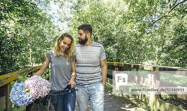 Couple walking on a wooden walkway with a bouquet of hydrangeas in the bicycle basket
