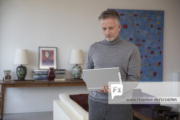 Geschäftsmann mit Laptop in der Wohnung