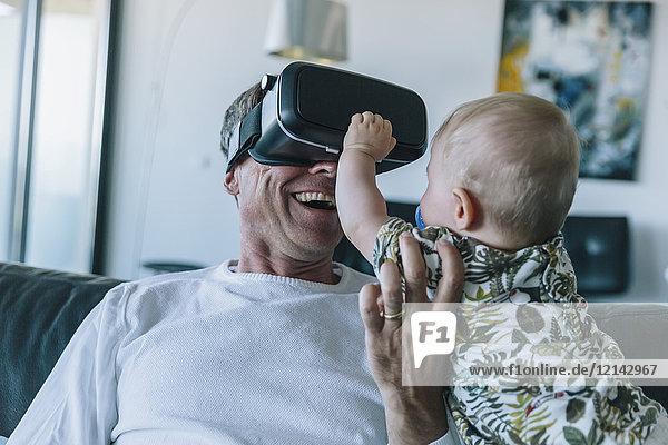 Glücklicher Mann mit Baby mit VR-Brille