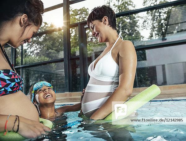 Zwei schwangere Frauen mit Tochter beim Wassergymnastik im Hallenbad