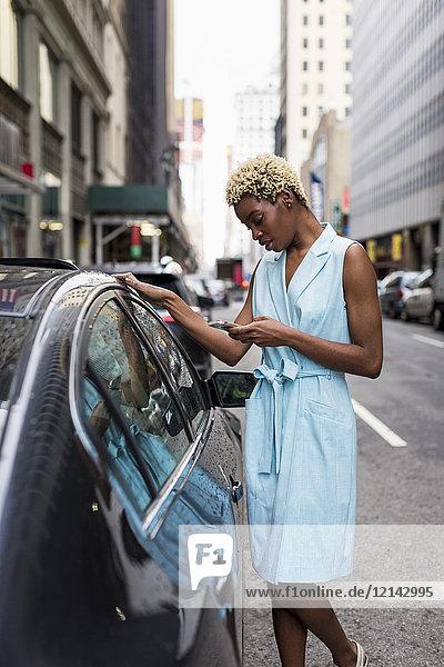 USA  New York  junge blonde Afroamerikanerin mit Smartphone