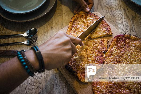 Knusprige hausgemachte Pizza mit dem Messer von Hand schneiden