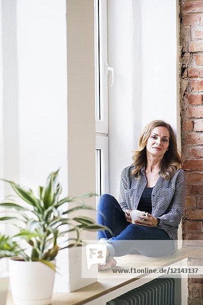 Frau sitzt zu Hause auf dem Fensterbrett und trinkt Kaffee.