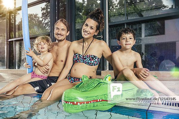 Porträt einer glücklichen Familie am Pool im Hallenbad