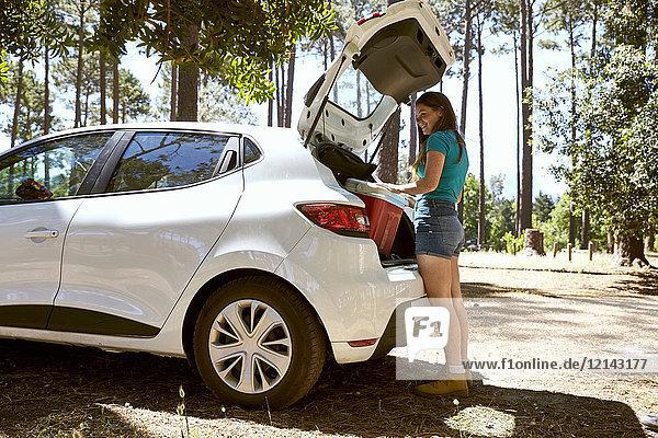 Lächelnde junge Frau beim Beladen eines Autos