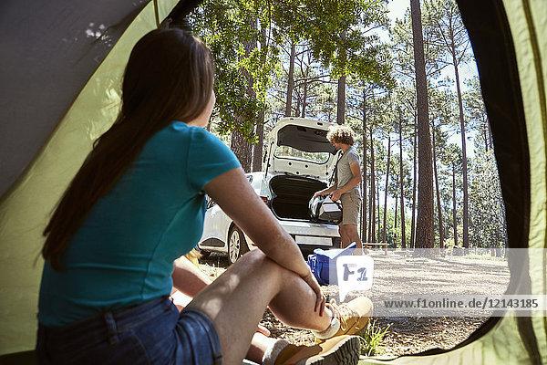 Junge Frau sitzt in einem Zelt und beobachtet ihren Freund beim Packen des Autos.