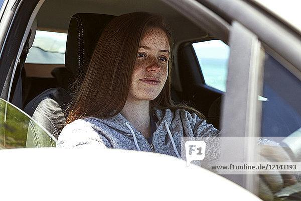 Porträt einer jungen Frau mit Sommersprossen im Auto