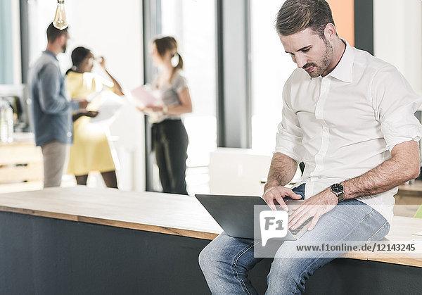 Geschäftsmann bei der Arbeit am Laptop im Büro mit Kollegen im Hintergrund