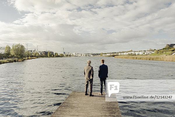Zwei Geschäftsleute stehen auf einem Steg am See