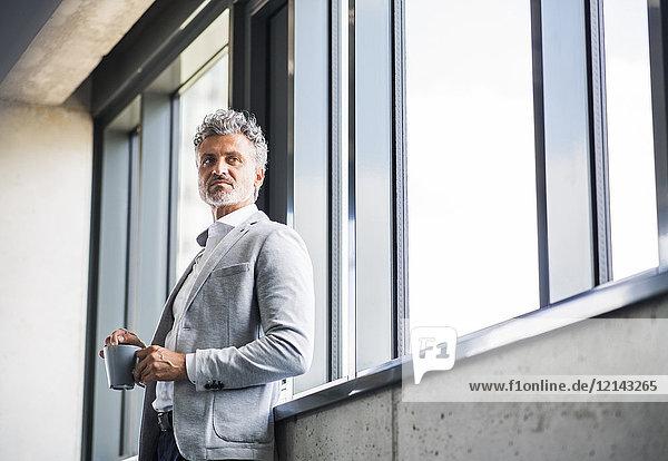 Erwachsener Geschäftsmann mit Kaffeetasse am Fenster
