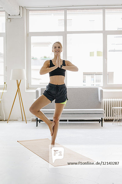Lächelnde junge Frau beim Yoga