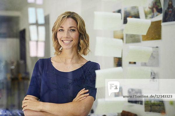 Porträt einer lächelnden blonden Frau  Scheibe mit Notizblöcken