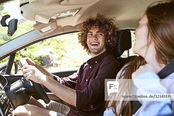 Lachender junger Mann  der Auto fährt und seine Freundin ansieht