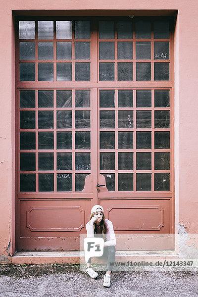 Modische junge Frau vor dem Eingangstor sitzend Modische junge Frau vor dem Eingangstor sitzend