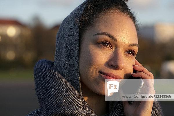 Porträt einer lächelnden jungen Frau auf dem Handy im Freien