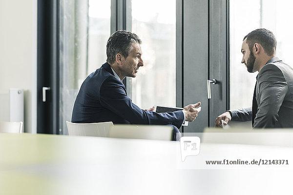 Zwei Geschäftsleute im Büro am Fenster