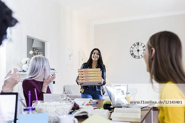 Junge Frauen bringen Pizza für Freunde mit  die zu Hause studieren.