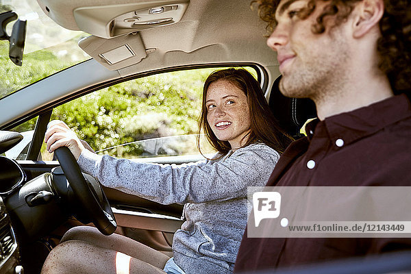 Lächelnde junge Frau fährt Auto und schaut ihren Freund an.