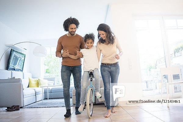 Eltern helfen der Tochter beim Einradfahren im Wohnzimmer