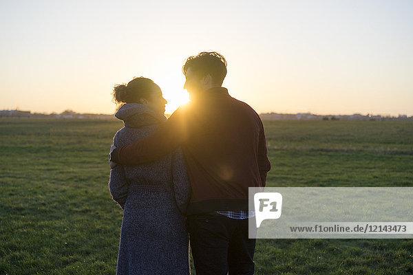 Junges Paar  das bei Sonnenuntergang auf einer Wiese spazieren geht.