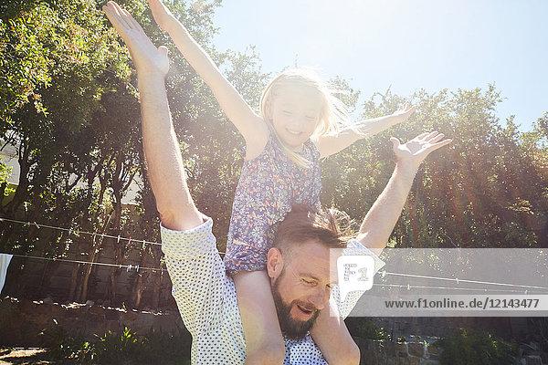 Glücklicher Vater mit Tochter auf den Schultern