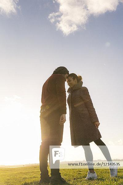 Zärtliches junges Paar steht bei Sonnenuntergang auf einer Wiese.