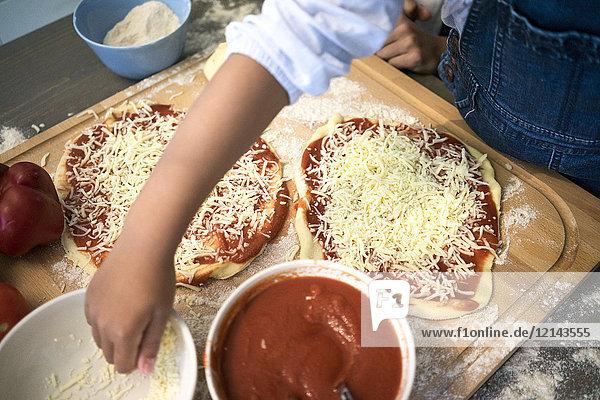 Mädchen in der Küche lernen  wie man Pizza backt  Käse bestreut