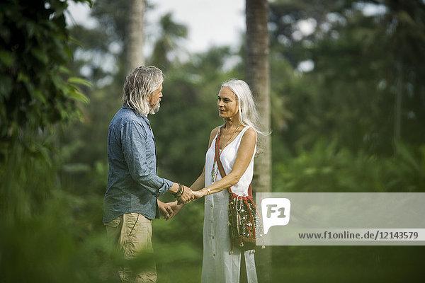 Liebevolles Seniorenpaar hält sich in tropischer Landschaft mit Palmen an den Händen