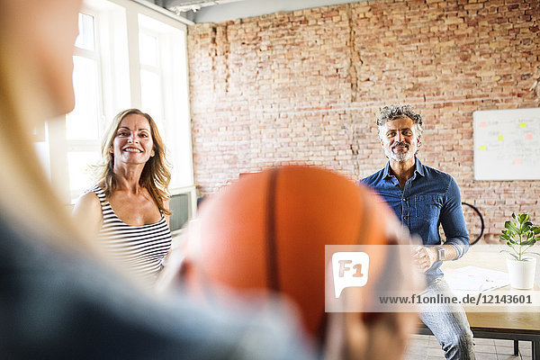 Lächelnde Kollegen mit Basketball im Büro