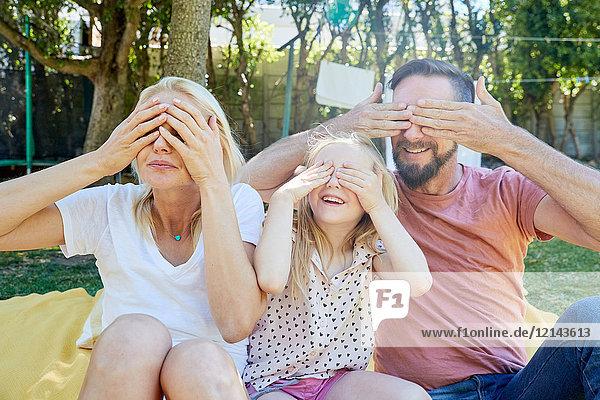 Porträt einer glücklichen Familie  die ihre Augen bedeckt.