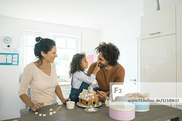 Familie bäckt Lebkuchenhaus zu Weihnachten mit Süßigkeiten  Tochter setzt Vereisung auf Vaters Nase