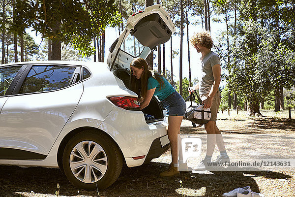 Junges Paar beim Verladen eines Autos im Wald