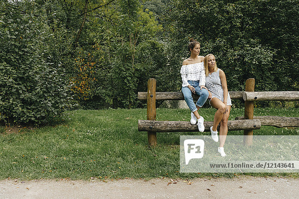 Zwei junge Frauen sitzen auf einem Zaun in einem Park.