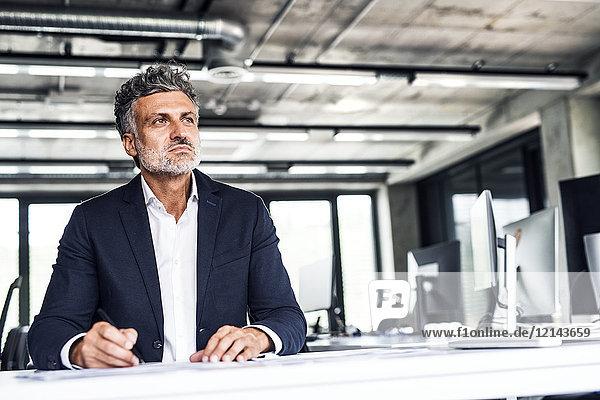 Ausgereifter Geschäftsmann im Bürodenken