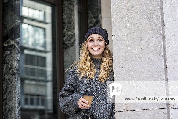 Porträt der modischen jungen Frau mit Kaffee zum Mitnehmen im Herbst