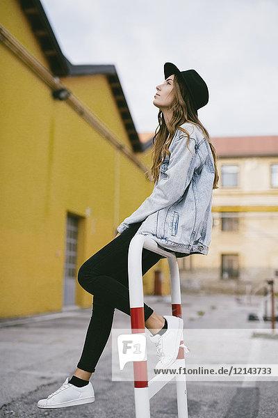 Modische junge Frau mit Hut auf Geländer sitzend