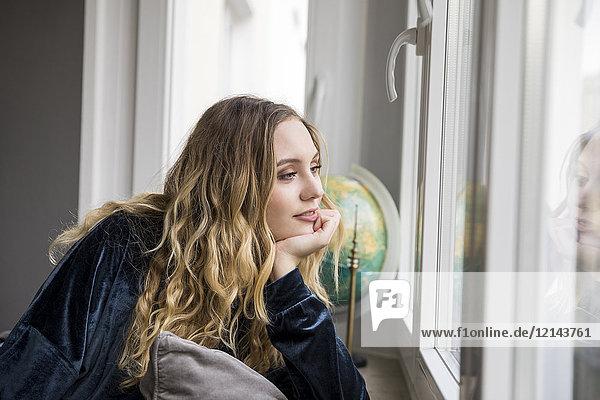 Porträt einer träumenden jungen Frau  die durchs Fenster schaut.
