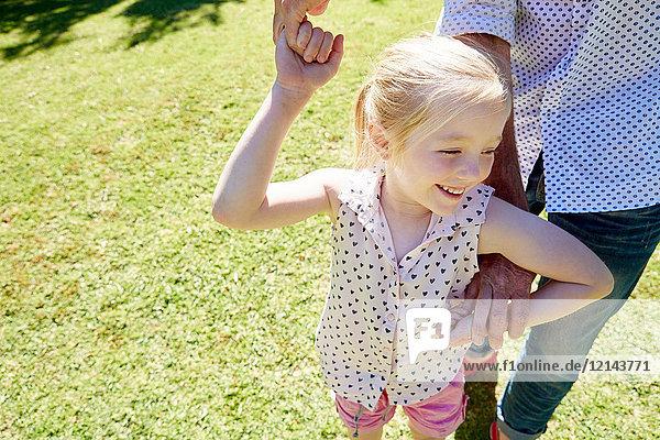 Lächelndes Mädchen auf Vaters Hand im Garten