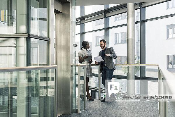 Geschäftsmann und Geschäftsfrau im Gespräch auf der Büroetage