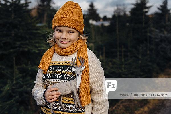 Little boy holding toy reindeer