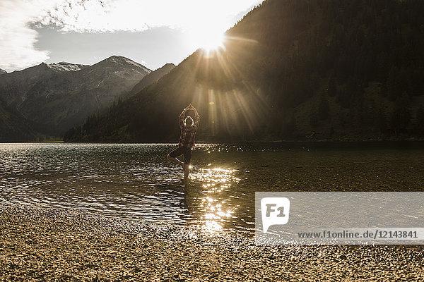 Österreich  Tirol  Wanderer in Yoga-Pose erfrischend im Bergsee