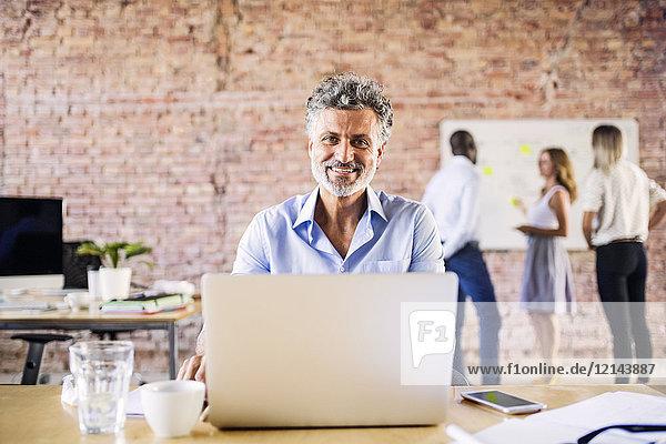 Portrait eines lächelnden Geschäftsmannes im Büro mit Kollegen im Hintergrund