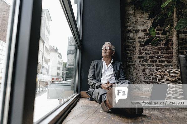Geschäftsmann sitzt auf dem Boden neben dem Fenster und macht eine Pause.