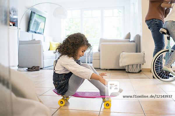 Kleines Mädchen auf dem Skateboard sitzend  Spaß habend