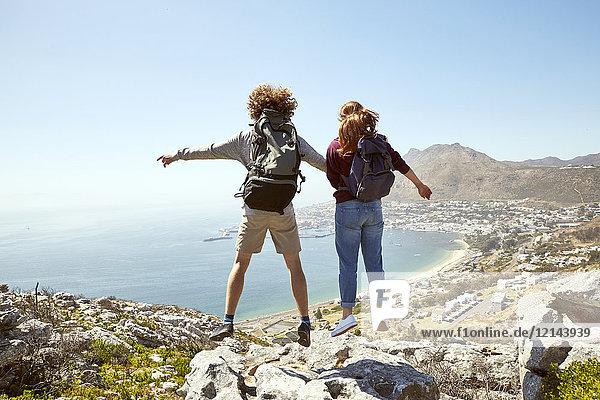 Südafrika  Kapstadt  junges Paar beim Springen an der Küste