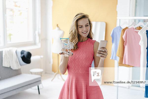 Lächelnde junge Frau im Modestudio macht Handyfoto vom Einkaufswagenmodell