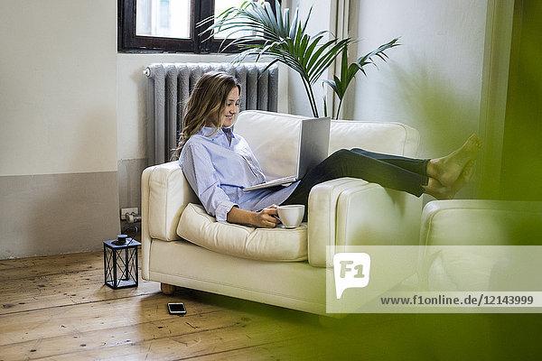 Lächelnde Frau auf der Couch zu Hause mit Laptop