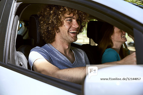 Lachendes junges Paar im Auto